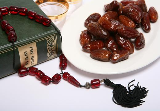Dates, a coffee cup waiting to be filled, beads, and a copy of the Holy Qur'an, all are symbolic of the Muslim fasting month of Ramadan and of the breaking of the fast each evening at Iftar.